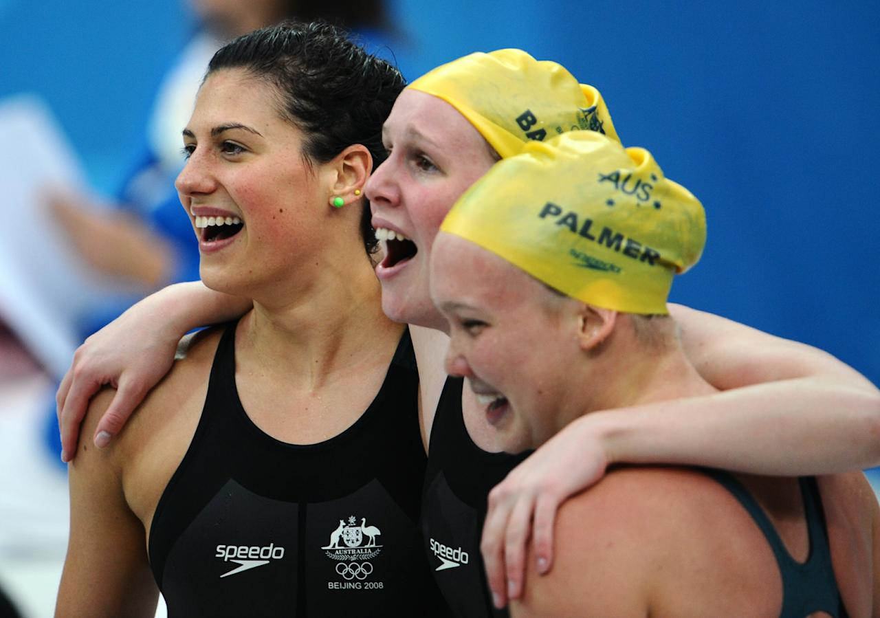 (FILES) In this August 14, 2008 photograph, Australia's Stephanie Rice, Bronte Barratt and Kylie Palmer celebrate after team member Linda Mackenzie arrived first in the women's 4x200m freestyle relay swimming final at the National Aquatics Center during the 2008 Beijing Olympic Games in Beijing.Five of the eight gold medals up for grabs on October 4, 2010, the first day of competition at the 2010 New Delhi Commonwealth Games, are in swimming.  AFP PHOTO / MARTIN BUREAU / FILES (Photo credit should read MARTIN BUREAU/AFP/Getty Images)