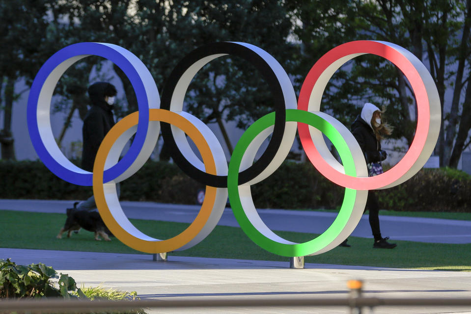 People wearing a face mask walk by the Olympic rings outside Japan Olympic Museum near National Stadium, where opening ceremony and many other events are planned for postponed Tokyo 2020 Olympics, Thursday, Jan. 21, 2021, in Tokyo. (AP Photo/Kiichiro Sato)