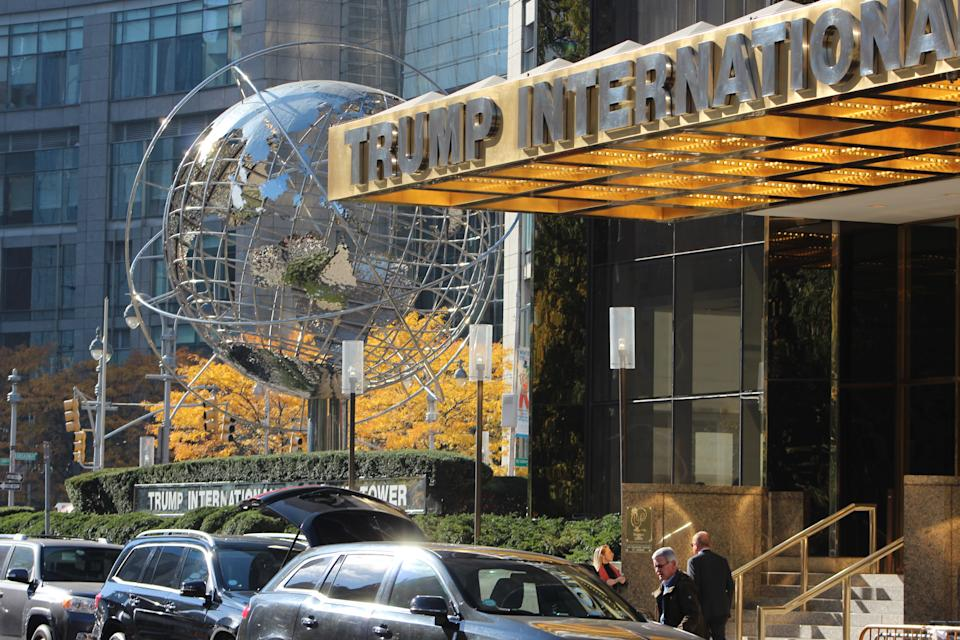 New York City, USA - November 14, 2016: Trump International Hotel and Tower in NYC at 1 Central Park West on Columbus Circle in front of the entrance of the building with several tourists or local people and cars lined up in front of the hotel.
