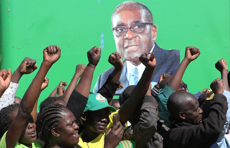 FILE - In this Tuesday, July 16, 2013, file photo, supporters welcome their leader President Robert Mugabe, seen on a poster, during a campaign rally in Chitungiwiza, Zimbabwe, about 20 kilometers (12.4 miles) south of Harare, Zimbabwe. Mugabe is on the campaign trail, seeking to extend his grip on Zimbabwe in an election next week that observers fear will be marred by fraud. But the opposition is gambling that there is enough discontent to unseat the wily political survivor, who has been in power for 33 years. (AP Photo/Tsvangirayi Mukwazhi, File)