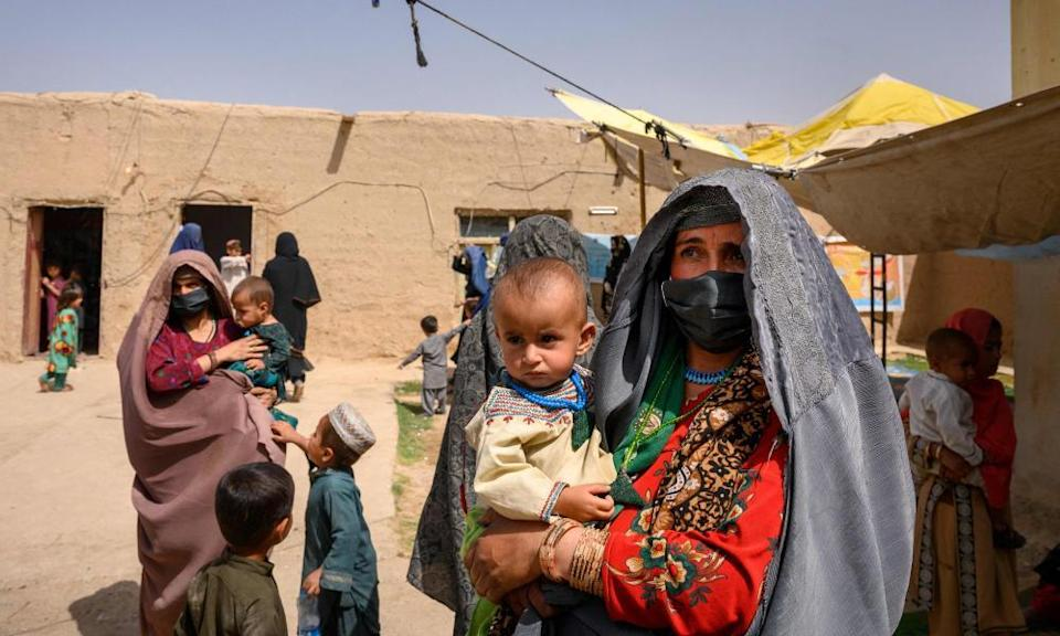 Women and children who fled fighting in Helmand province wait to see a doctor at a mobile clinic