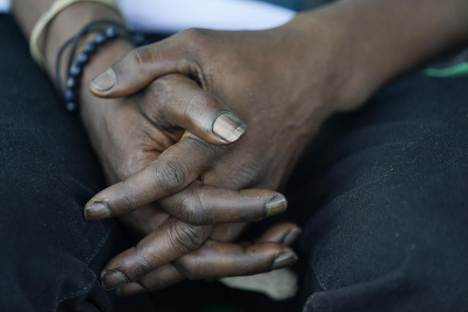 Jerry Simmons, 49, holds his hands together before entering a new mobile help unit run by Assisted Recovery Centers of America in a church parking lot in St. Louis on Thursday, May 20, 2021. Simmons sometimes imagines himself lying in one of those vacant houses where he sleeps, dead for days from an overdose before anyone discovers him. (AP Photo/Brynn Anderson)