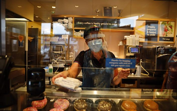 An employee wearing PPE at the counter of a Greggs bakery in London, which reopened 800 of its UK stores today - AFP