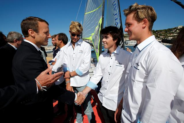 "French President Emmanuel Macron speaks with athletes as he visits the site of the future Olympic Sailing venue (Voile Olympique) at the ""Marina Olympique"" nautical base in Marseille, France, after the decision for Paris to host of the 2024 Summer Olympics Games, September 21, 2017. REUTERS/Jean-Paul Pelissier"