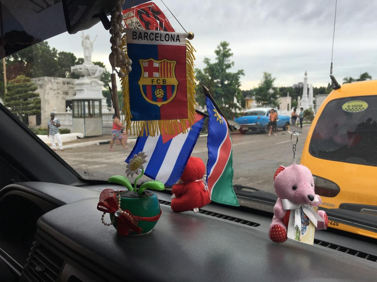 <p>Knickknacks and flags on the dashboard of a minivan taxi in the fishing village of Cojímar, which is about six miles east of Havana. <i>(Photo: Lauren Johnston/Yahoo News)</i></p>