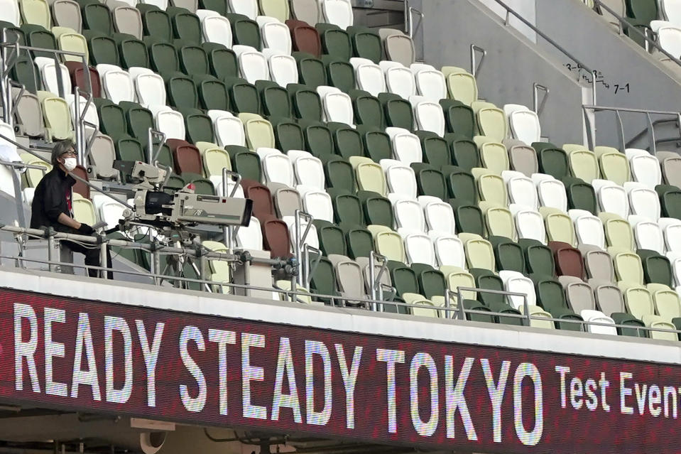 A TV cameraman sits beside empty spectators' seats during an athletics test event for Tokyo 2020 Olympics Games at the National Stadium, in Tokyo, Japan, Sunday, May 9, 2021. Tens of thousands of visiting athletes, officials and media are descending on Japan for a Summer Olympics unlike any other. There will be no foreign fans, no local fans in Tokyo-area venues. A surge of virus cases has led to yet another state of emergency. (AP Photo/Shuji Kajiyama)
