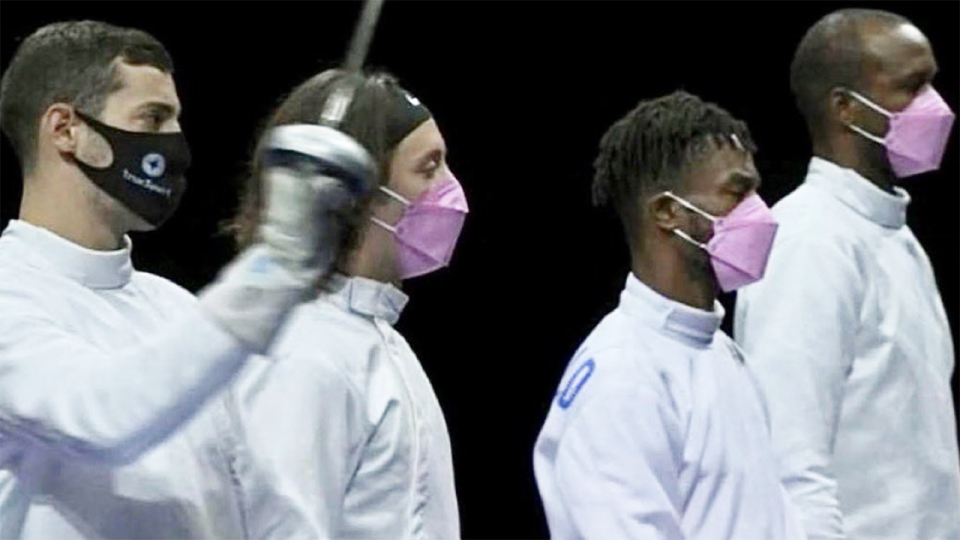 Three members of the USA fencing team wear pink masks in protest against teammate Alen Hadzic, wearing a black mask.