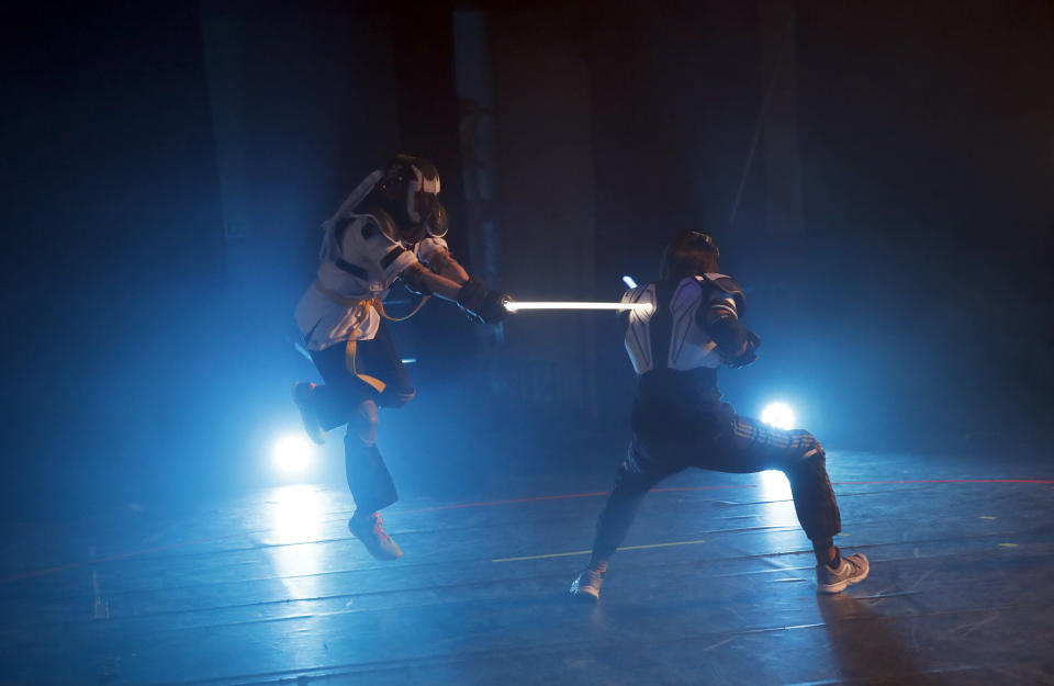 In this Sunday, Feb. 10, 2019, photo, competitors battle during the national lightsabers tournament in Beaumont-sur-Oise, north of Paris. In France, lightsaber fighting is an official sport, recognized as such by the French Fencing Federation. The sport's practitioners, many but not all of the fans of 'Stars Wars,' have had to build the discipline's competition rules almost from scratch. (AP Photo/Christophe Ena)