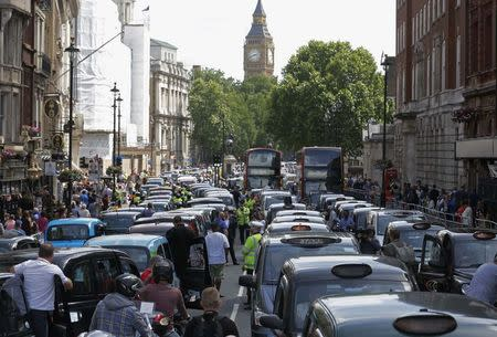 Taxi drivers block the road in Whitehall in central London June 11, 2014. REUTERS/Luke MacGregor