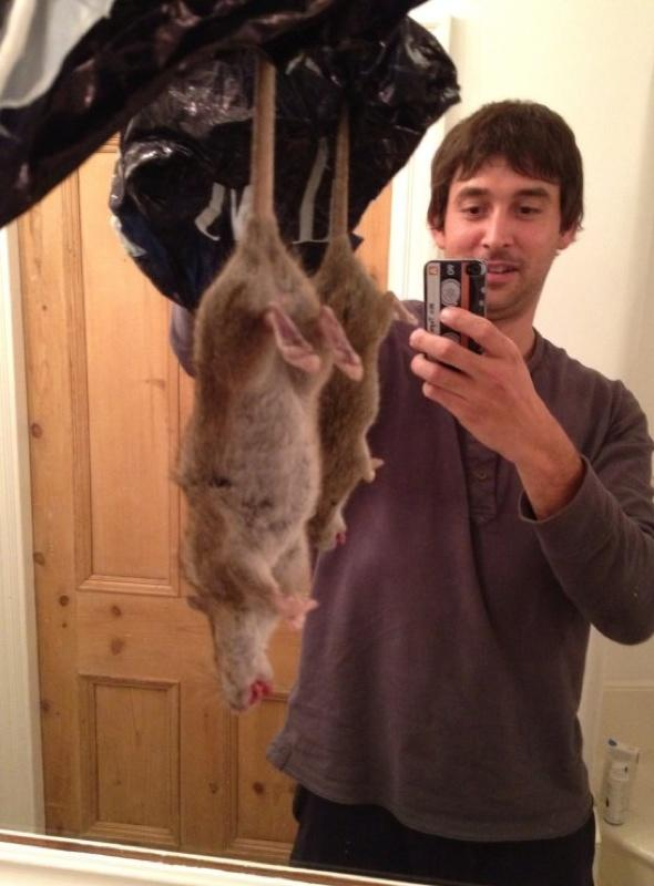 Adrian Whitaker holding the rat he caught and killed.