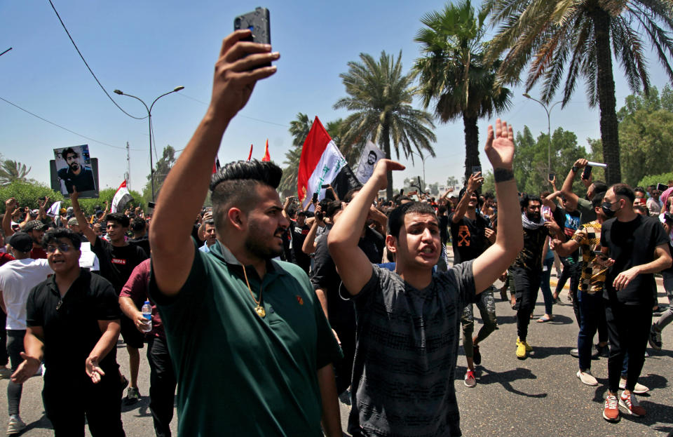 Anti-government protesters chant slogans as they hold posters of slain activists outside the Green Zone area which houses the seat of the country's government and foreign embassies, in Baghdad, Iraq, Tuesday, May 25, 2021. Hundreds of Iraqi protesters have taken to the streets of Baghdad to decry a recent spike in assassinations targeting outspoken activists and journalists. (AP Photo/Khalid Mohammed)