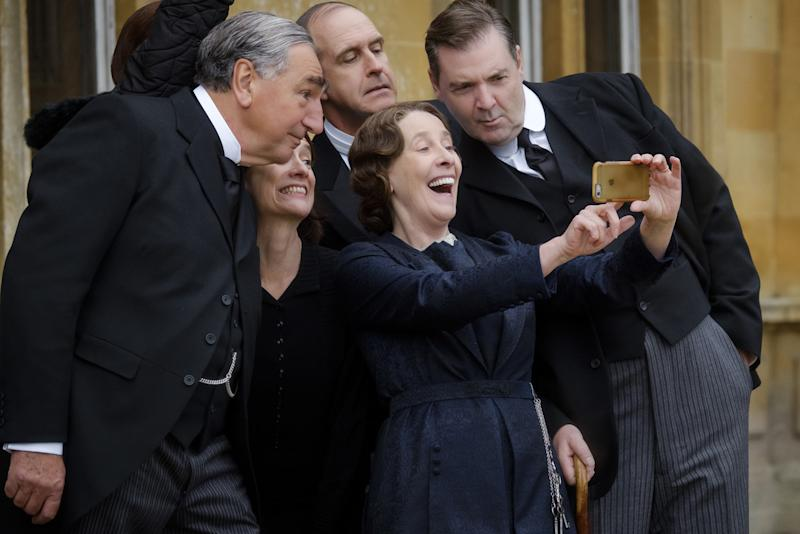 Jim Carter, Raquel Cassidy, Kevin Doyle, Phyllis Logan, and Brendan Coyle taking a selfie with an iphone on the set of downton abbey