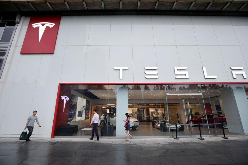 FILE PHOTO: People walk past a showroom outside Tesla China headquarters in Beijing