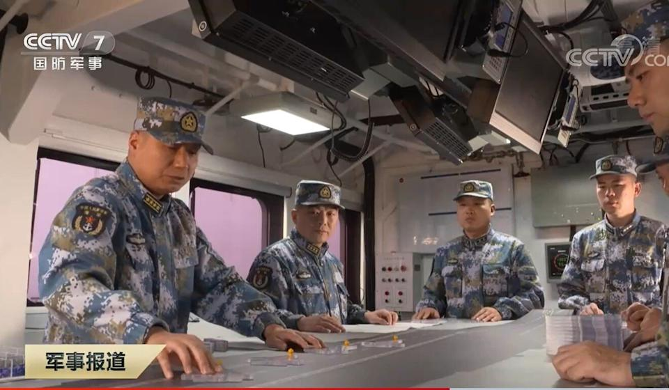 """Lai Yijun, captain of the Shandong (left), and political commissar Song Wenjun (second left) play """"carrier chess"""" using small models of J-15 fighters. Source: CCTV"""