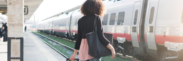 Young woman waiting for the train on station platform