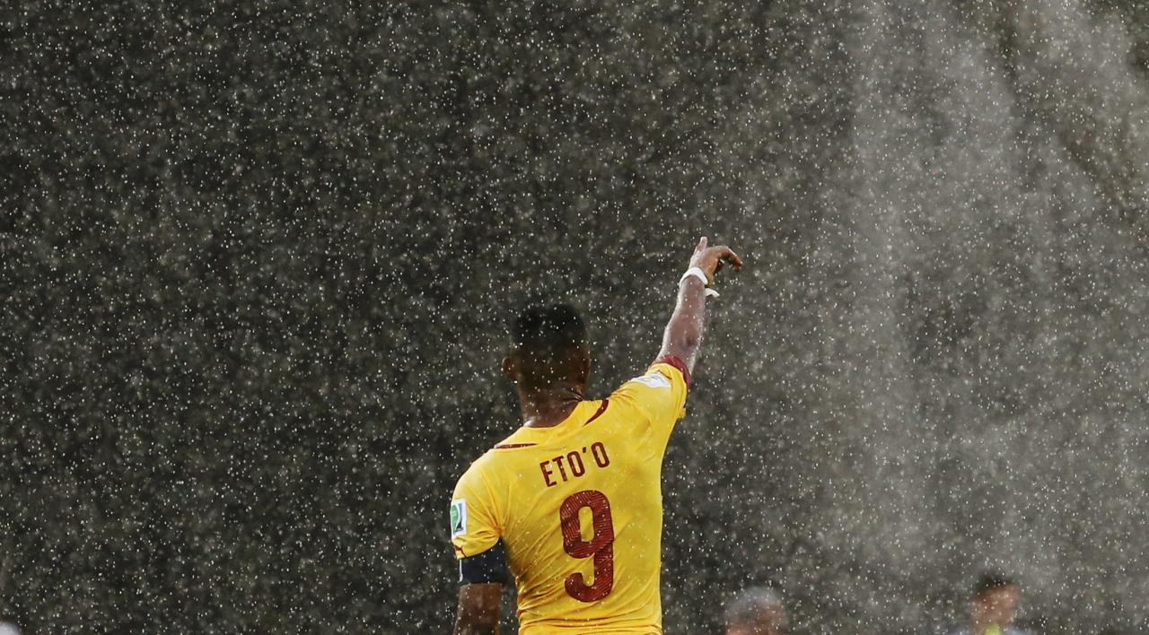 Cameroon's Samuel Eto'o gestures in the rain during their 2014 World Cup Group A soccer match against Mexico at the Dunas arena in Natal June 13, 2014. REUTERS/Jorge Silva (BRAZIL - Tags: TPX IMAGES OF THE DAY SOCCER SPORT WORLD CUP)