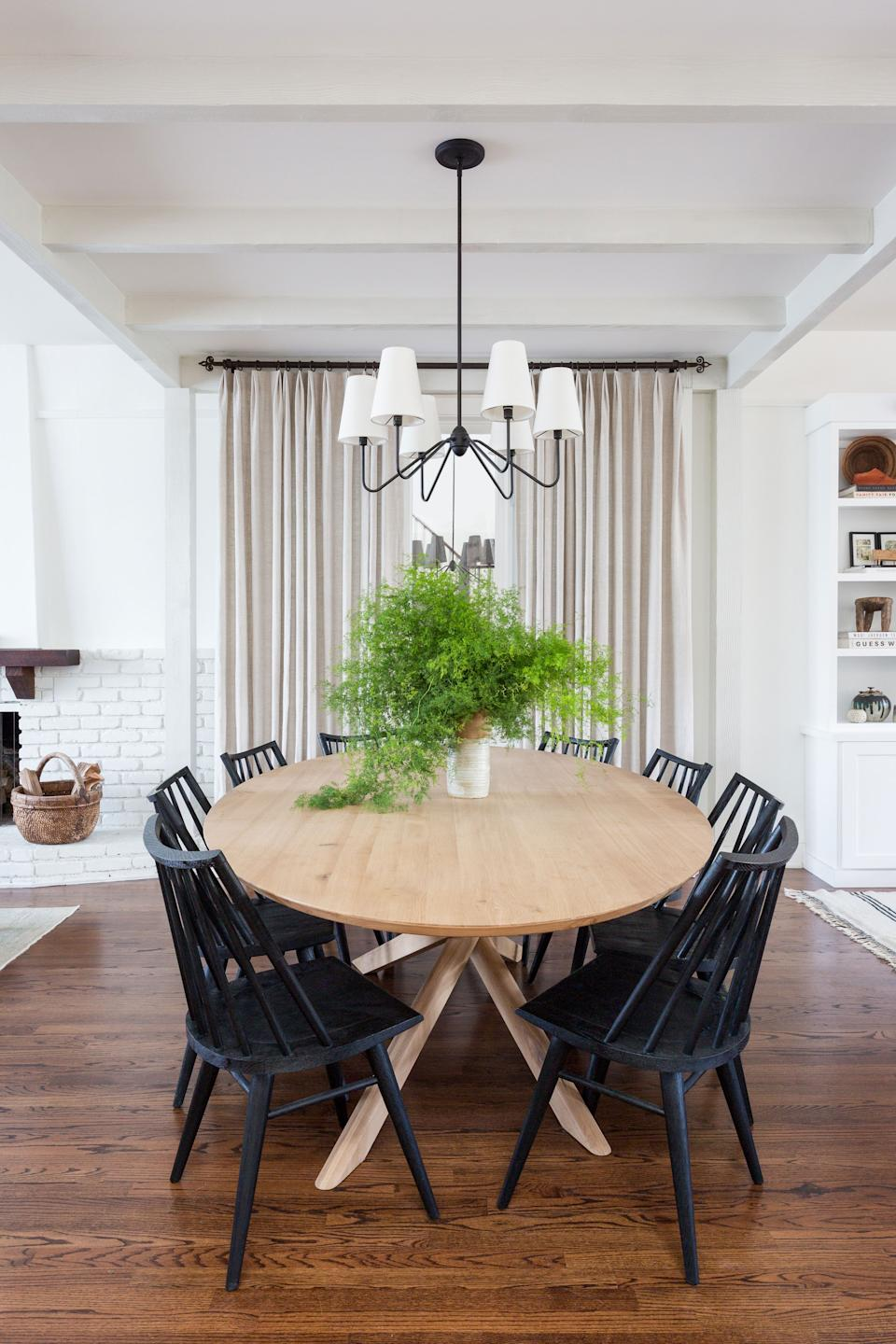 "<div class=""caption""> The actor Sam Page and his spouse, Cassidy Elliott, enlisted the help of close family friend Allie Boesch, of Allie Boesch Designs, to remake their new Pacific Palisades home. The dining room separates the family room from the more formal living room. ""You truly feel like it's the axis of the house when you're sitting at the table,"" says Page. The large table is from <a href=""https://www.ethnicraft.com/"" rel=""nofollow noopener"" target=""_blank"" data-ylk=""slk:Ethnicraft"" class=""link rapid-noclick-resp"">Ethnicraft</a>, with chairs from <a href=""https://www.mcgeeandco.com/"" rel=""nofollow noopener"" target=""_blank"" data-ylk=""slk:McGee & Co"" class=""link rapid-noclick-resp"">McGee & Co</a>. The pendant overhead is from <a href=""https://www.rejuvenation.com/"" rel=""nofollow noopener"" target=""_blank"" data-ylk=""slk:Rejuvenation"" class=""link rapid-noclick-resp"">Rejuvenation</a>. </div>"