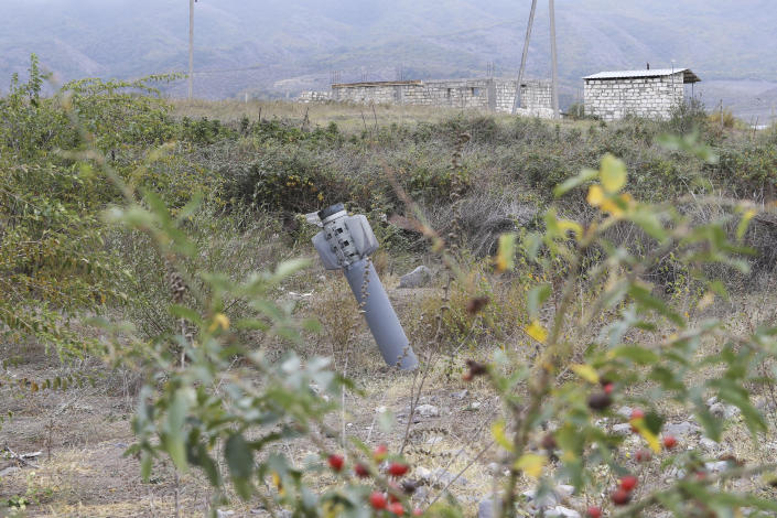 An unexploded projectile of multiple rocket launcher stuck into land near a settlement in self-proclaimed Republic of Nagorno-Karabakh, Azerbaijan, Thursday, Oct. 1, 2020. Two French and two Armenian journalists were injured Thursday in the area of heavy fighting between Armenian and Azerbaijani forces. (Hayk Baghdasaryan/Photolure via AP)