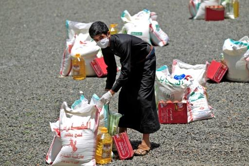 A Yemeni youth carries a portion of food aid in Yemen's capital Sanaa on May 17