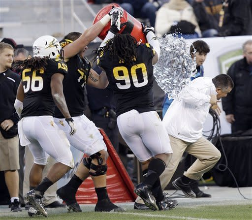 Arizona State head coach Todd Graham, right, is doused after a 62-28 win over Navy during the Fight Hunger Bowl NCAA college football game in San Francisco, Saturday, Dec. 29, 2012. (AP Photo/Marcio Jose Sanchez)