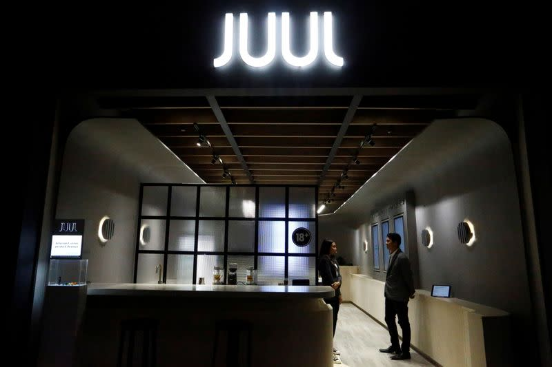 Shopkeepers stand inside a Juul shop at a shopping mall in Jakarta