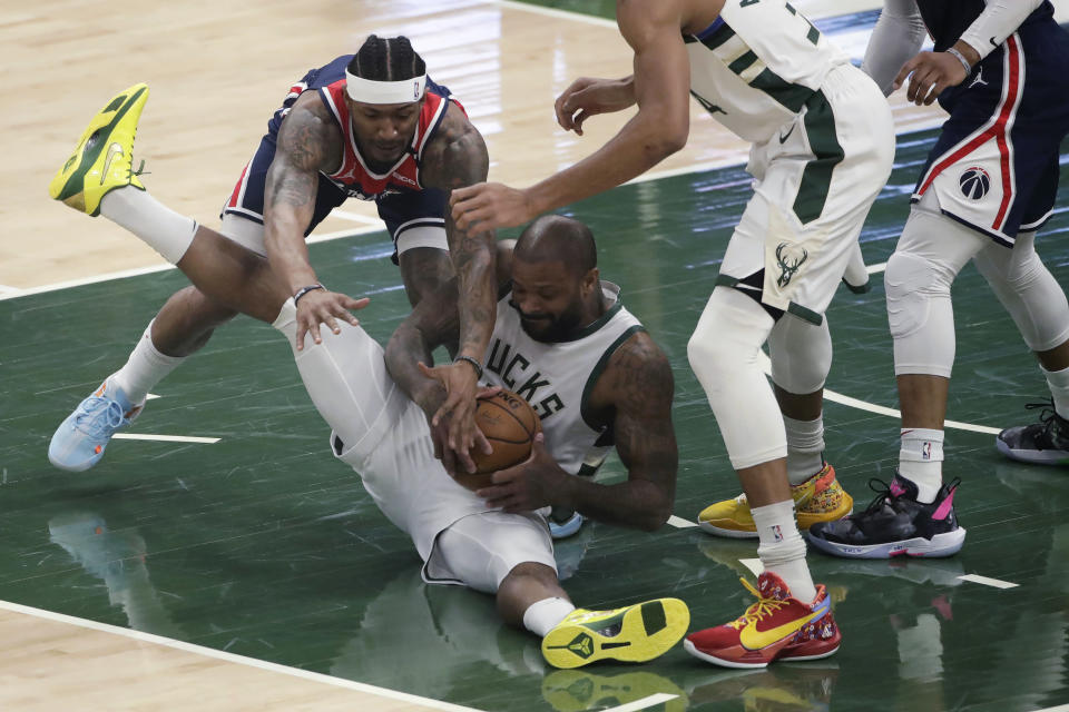 Milwaukee Bucks' P.J. Tucker and Washington Wizards' Bradley Beal compete for possession of the ball during the first half of an NBA basketball game Wednesday, May 5, 2021, in Milwaukee. (AP Photo/Aaron Gash)