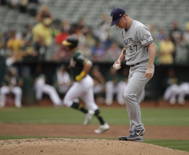 Milwaukee Brewers pitcher Chase Anderson, right, waits for Oakland Athletics' Chad Pinder to run the bases after hitting a home run in the third inning of a baseball game Thursday, Aug. 1, 2019, in Oakland, Calif. (AP Photo/Ben Margot)