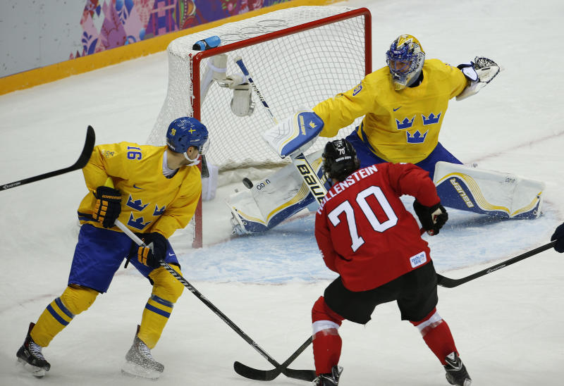 Sweden goaltender Henrik Lundqvist blocks a shot by Switzerland forward Denis Hollenstein as Sweden forward Marcus Kruger defends in the first period of a men's ice hockey game at the 2014 Winter Olympics, Friday, Feb. 14, 2014, in Sochi, Russia. (AP Photo/Julio Cortez)