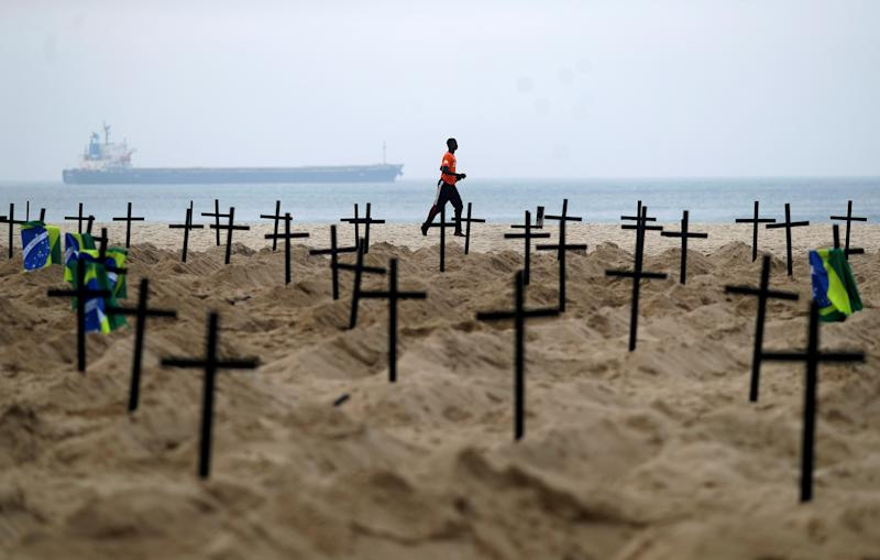 A man runs past the one hundred graves which were dug by activists of the NGO Rio de Paz on Copacabana beach symbolising the dead from the coronavirus disease (COVID-19), in Rio de Janeiro, Brazil, June 11, 2020. REUTERS/Pilar Olivares TPX IMAGES OF THE DAY - RC207H9HAK1Z