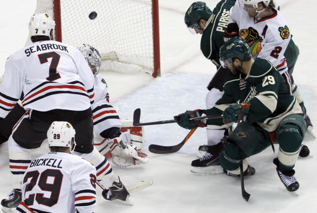 Minnesota Wild right wing Jason Pominville (29) scores on Chicago Blackhawks goalie Corey Crawford in front of Blackhawks defenseman Brent Seabrook (7) during the second period of Game 4 of an NHL hockey second-round playoff series in St. Paul, Minn., Friday, May 9, 2014. (AP Photo/Ann Heisenfelt)