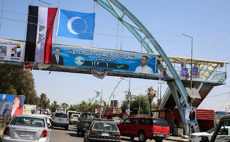 A picture taken on April 30, 2018, shows an electoral banner for the Iraqi Turkmen Front hanging beneath the flags of Iraq (L) and the Iraqi Turkmen (C) above a pedestrian crossing in the oil-rich and multi-ethnic northern city of Kirkuk (AFP Photo/SABAH ARAR)