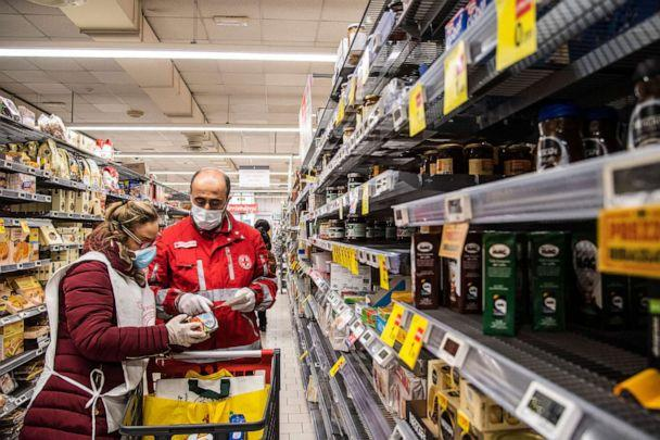 PHOTO: Volunteers from the Italian Red Cross shop at a supermarket for the home delivery service of groceries and medicines to people who are alone and unable to move during the coronavirus outbreak in Rome, Italy, March 24, 2020. (Alessandro Serrano/AGF/REX/Shutterstock)