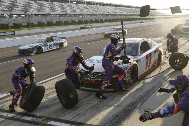 Crew members hustle to service the car of Denny Hamlin in a pit stop during a NASCAR Cup Series auto race at Pocono Raceway, Sunday, June 28, 2020, in Long Pond, Pa. (AP Photo/Matt Slocum)