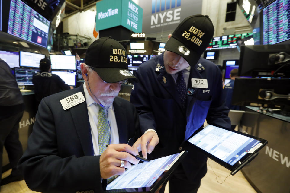"""Traders Peter Tuchman, left, and his son Benjamin Tuchman, wear """"Dow 28,000"""" hats at the close of trading on the floor of the New York Stock Exchange. (Photo: AP Photo/Richard Drew)"""
