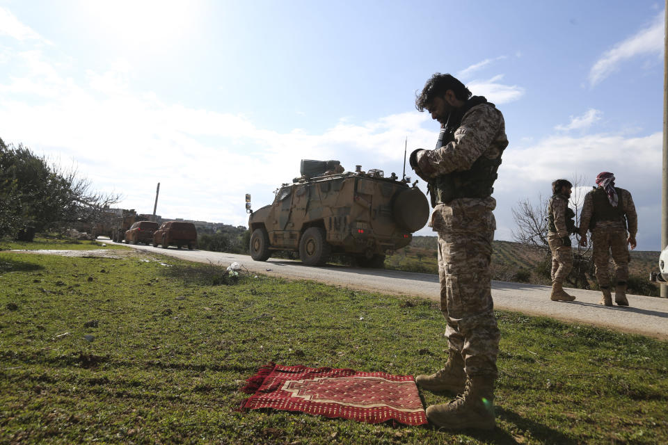 Syrian rebel fighter prays as a Turkish military convoy stops in Idlib province, Syria, Saturday, Feb. 22, 2020. A Turkish soldier was killed in Syria's northwest Idlib province, state-run Anadolu news agency reported Saturday. (AP Photo/Ghaith Alsayed)