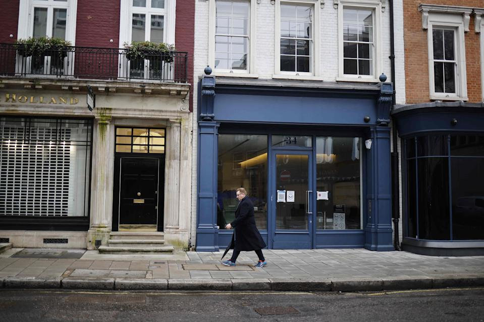 <p>A pedestrian passes closed shop fronts in the Mayfair area of central London as life continues under Britain's third coronavirus lockdown</p> (AFP via Getty Images)