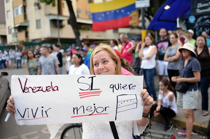 """""""Venezuela wants to live better"""" -- voters celebrate in Caracas after taking part in an opposition-organized ballot challenging embattled Venezuelan President Nicolas Maduro's plan to rewrite the constitution (AFP Photo/FEDERICO PARRA )"""
