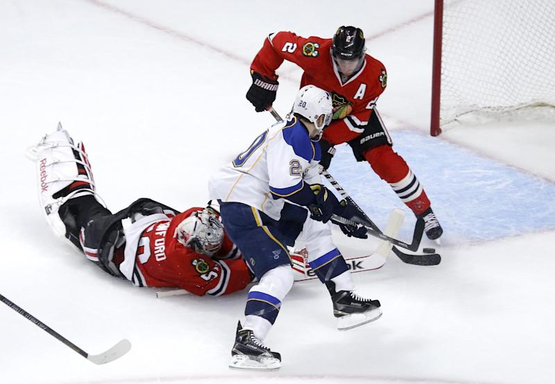 Chicago Blackhawks goalie Corey Crawford, left, tries to keep St. Louis Blues left wing Alexander Steen (20) from getting a shot on goal as defenseman Duncan Keith also defends during the first period in Game 3 of a first-round NHL hockey Stanley Cup playoff series game Monday, April 21, 2014, in Chicago. (AP Photo/Charles Rex Arbogast)