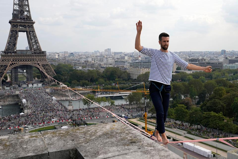 French slackliner Nathan Paulin performs on the second time on a 70-meter-high slackline between the Eiffel Tower and the Chaillot Theater across the Seine River, in Paris Sunday, Sept. 19, 2021.