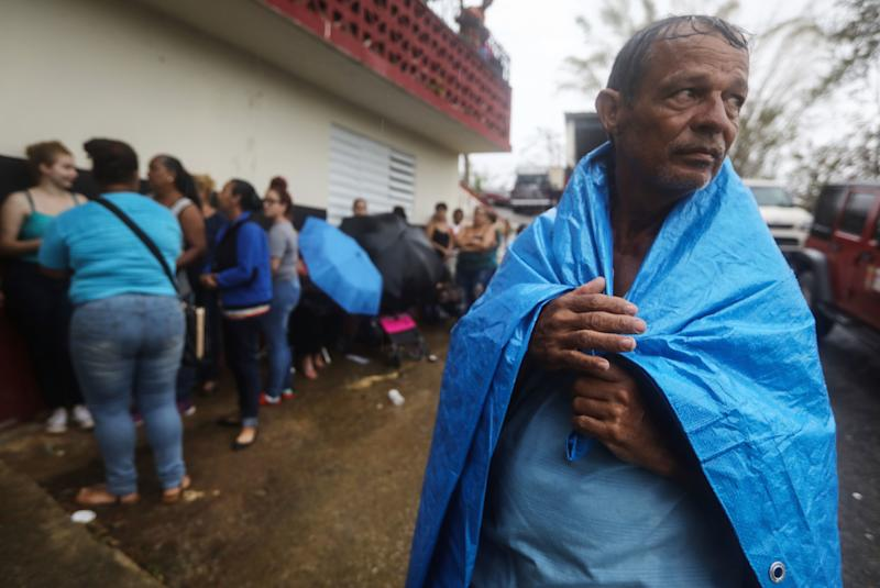 Arian Rodriguez covers himself in a tarp as residents of Juyuya wait in the rain for more than seven hours to register with FEMA. (Mario Tama via Getty Images)