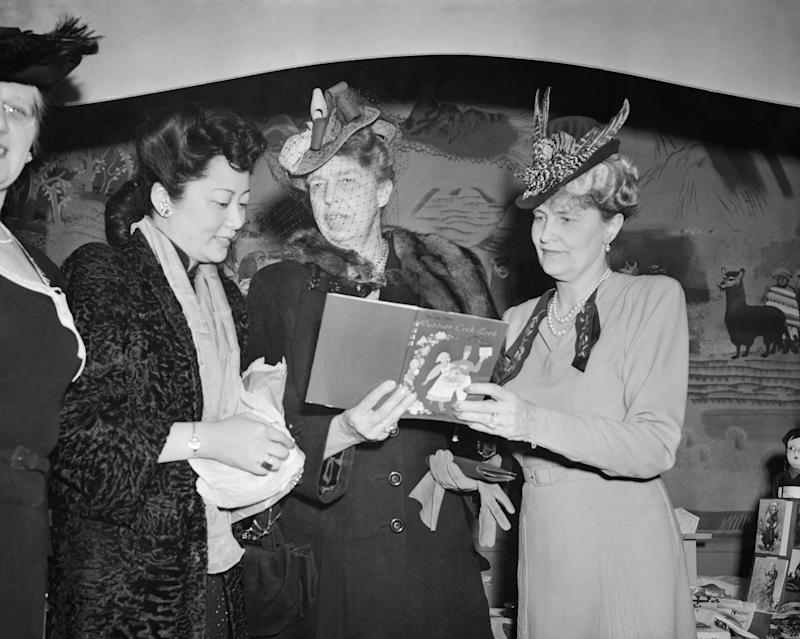 (Original Caption) Mrs. Eleanor Roosvelt, wife of the president, examines a Russian cook book outside the Russian booth at the opening of the United War relief Christmas Bazaar at the Statler Hotel in Washington with the first lady are Mme T.Y.Soong, wife of the Chines Foreign Minister (left), and Mrs. Joseph Davies, wife of the fromer Ambassador to Moscow.