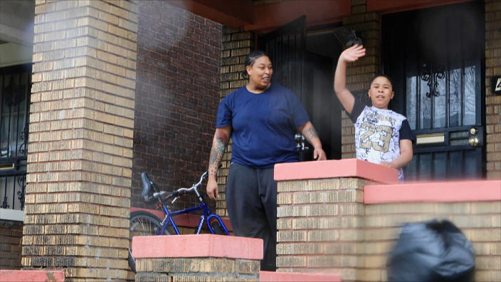 Lasheena Price and her son, Larrone, 9, a second grader at Detroit's New Paradigm Loving Academy, wave goodbye to Dungey. (Jake Whitman / NBC News)