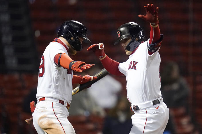 Boston Red Sox's Enrique Hernandez, right, dances with Alex Verdugo after crossing home plate while celebrating his solo home run during the eighth inning of a baseball game against the Detroit Tigers at Fenway Park, Tuesday, May 4, 2021, in Boston. (AP Photo/Charles Krupa)