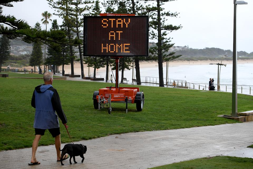 A man walks his dog in Sydney's Northern Beaches as a public health message is seen on temporary signage at Dee Why.