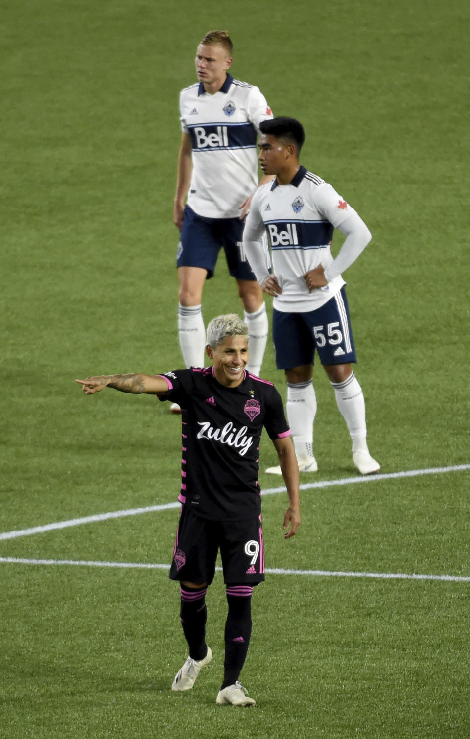Seattle Sounders forward Raul Ruidiaz, bottom, celebrate after the Sounders scored a goal as Vancouver Whitecaps midfielder Michael Baldisimo, center, and midfielder Andy Rose, top, stand nearby during the second half of an MLS soccer match in Portland, Ore., Tuesday, Oct. 27, 2020. (AP Photo/Steve Dykes)