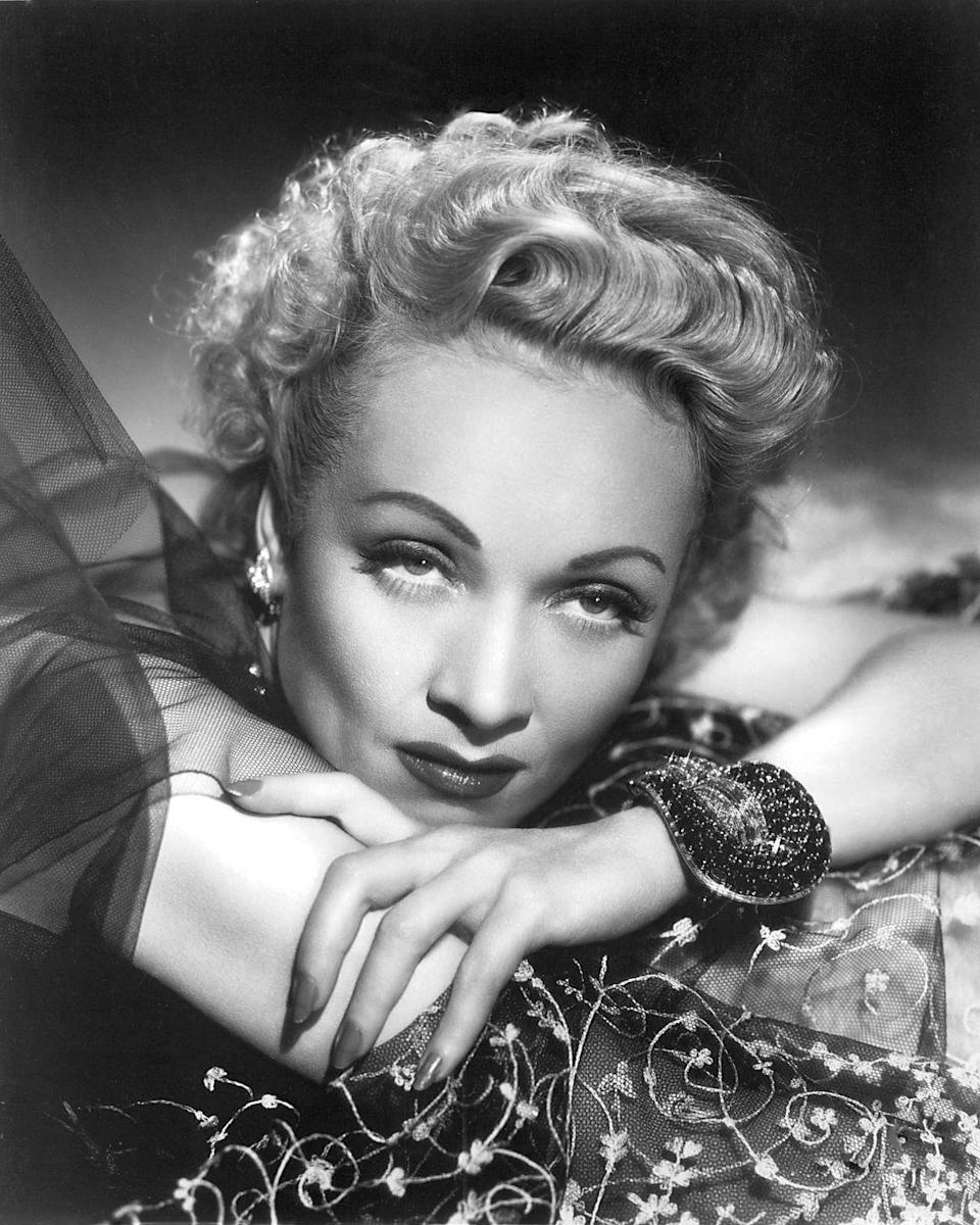 """<p>Dietrich would sometimes wear her personal jewelry in her roles. Here, in Alfred Hitchcock's <em>Stage Fright</em> (the director loved using jewelry in notable ways in his films), Dietrich wears her <a href=""""https://www.vancleefarpels.com/us/en/home.html"""" rel=""""nofollow noopener"""" target=""""_blank"""" data-ylk=""""slk:Van Cleef & Arpels"""" class=""""link rapid-noclick-resp"""">Van Cleef & Arpels</a> Jarretière ruby and diamond bracelet, designed for her by Louis Arpels. </p>"""