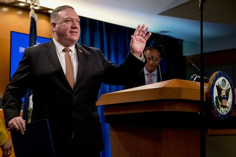 Secretary of State Mike Pompeo waves as he leaves a news conference in which he announced new action against Chinese telecom giant Huawei