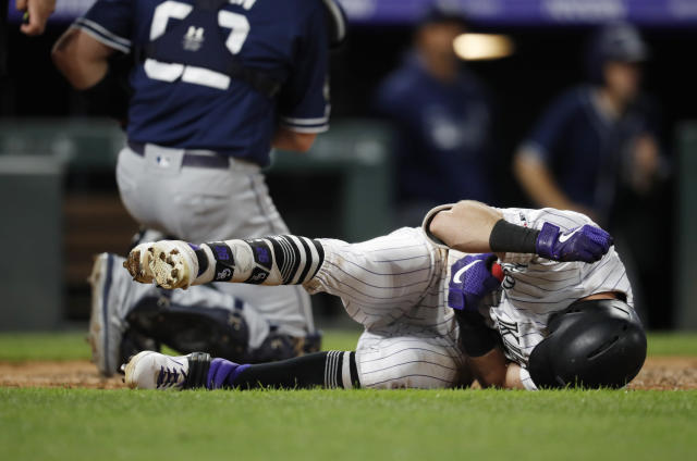 Colorado Rockies' David Dahl reacts after getting hit by a pitch thrown by San Diego Padres relief pitcher Robbie Erlin during the fifth inning of a baseball game Saturday, June 15, 2019, in Denver. (AP Photo/David Zalubowski)