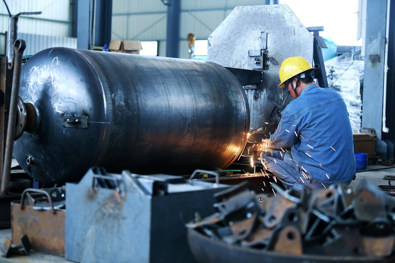 A worker welds a pressure vessel at a company manufacturing industrial equipment in Nantong, Jiangsu province, China June 19, 2018. Picture taken June 19, 2018. REUTERS/Stringer ATTENTION EDITORS - THIS IMAGE WAS PROVIDED BY A THIRD PARTY. CHINA OUT.