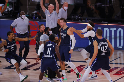Luka Doncic, center, of the Dallas Mavericks, celebrates his game-winning three-point basket with teammates after defeating the Los Angeles Clippers in overtime of Game 4 of an NBA basketball first-round playoff series, Sunday, Aug. 23, 2020, in Lake Buena Vista, Fla. (Kevin C. Cox/Pool Photo via AP)